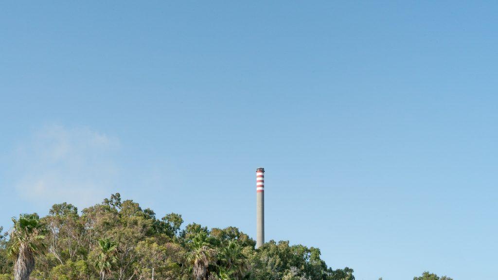 La chimenea que no puede ser escondida de la Central Térmica de Los Barrios. Es una barrera para evitar la denuncia social por parte de la población sobre la crisis ambiental.